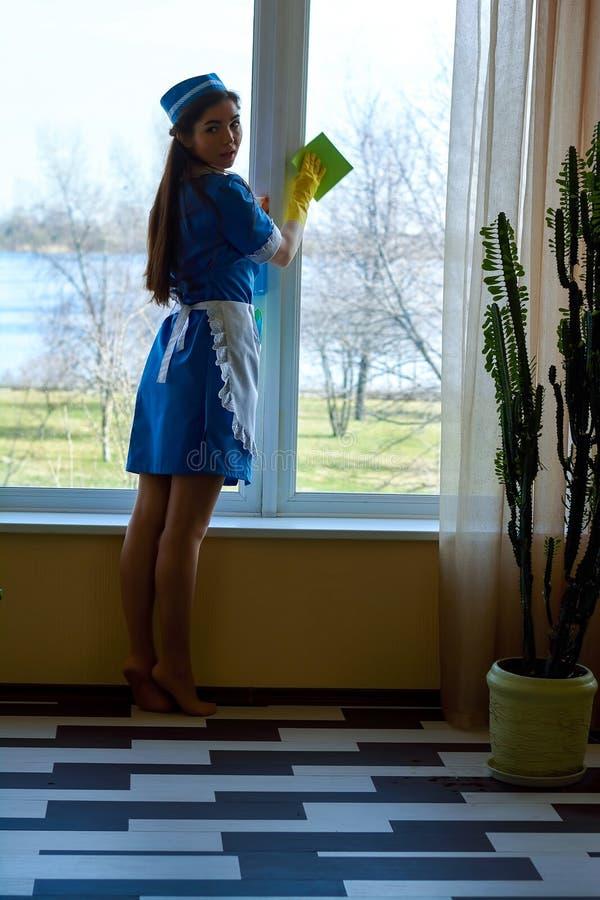 俏丽的佣人清洁窗口 库存图片