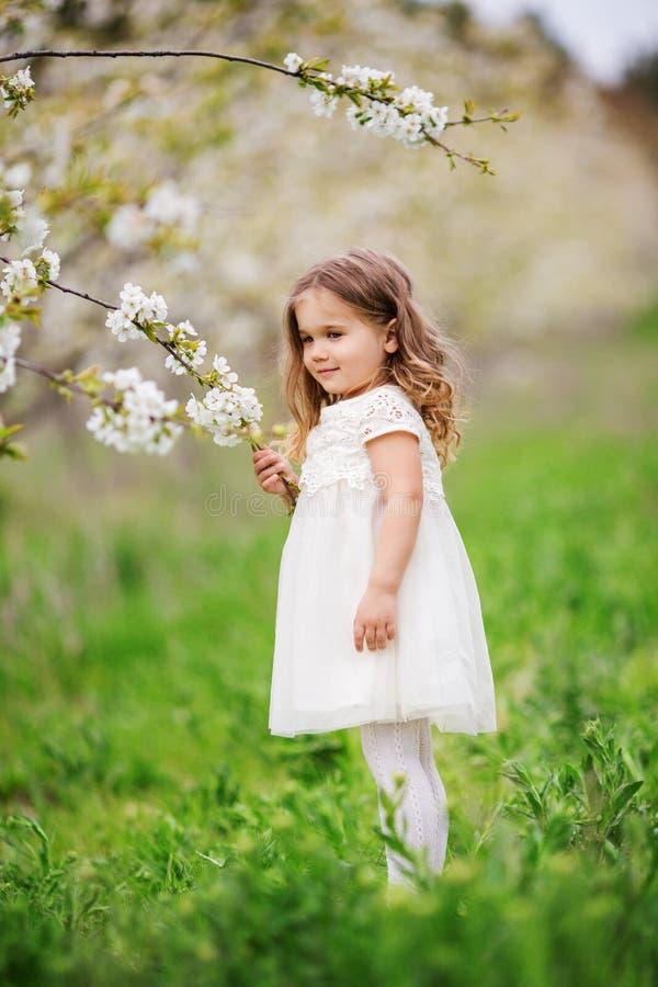 俏丽的儿童女孩在开花春天庭院里 免版税库存照片