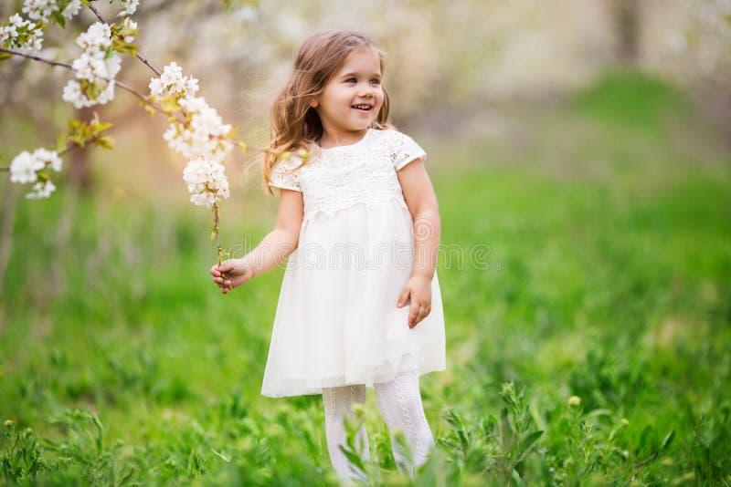 俏丽的儿童女孩在开花春天庭院里 免版税图库摄影