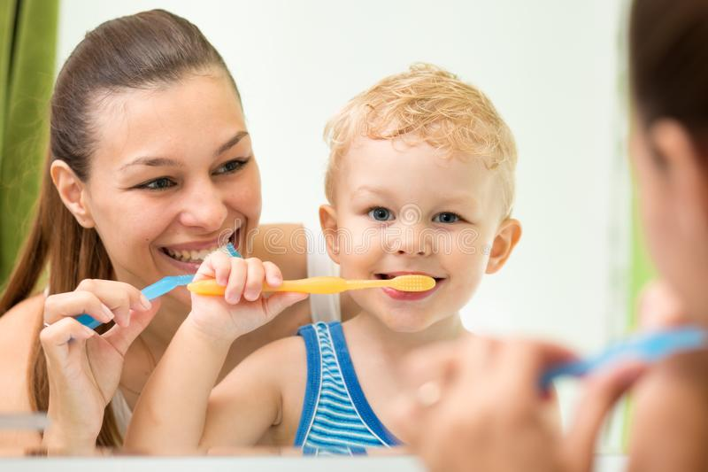 俏丽的刷他们的牙和看miroor的妇女和她的儿子在卫生间里 库存图片