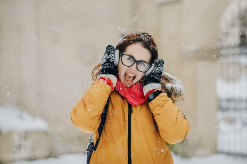 俏丽的可爱的女孩行家在冬天 她听到在耳机的音乐 青年街道时尚 驱动乐趣爬犁冬天 图库摄影