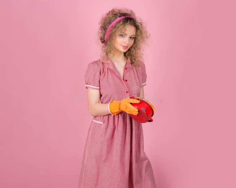 俏丽的在手套的妇女洗涤肮脏的罐 主妇在膳食以后洗涤  我的厨房在好手里 免版税库存图片