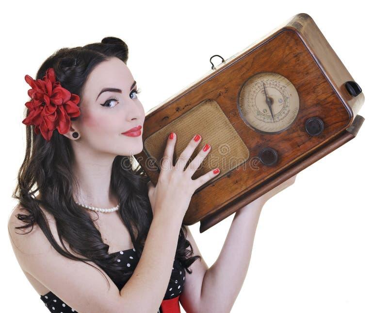 俏丽的在收音机的女孩听的音乐 库存照片