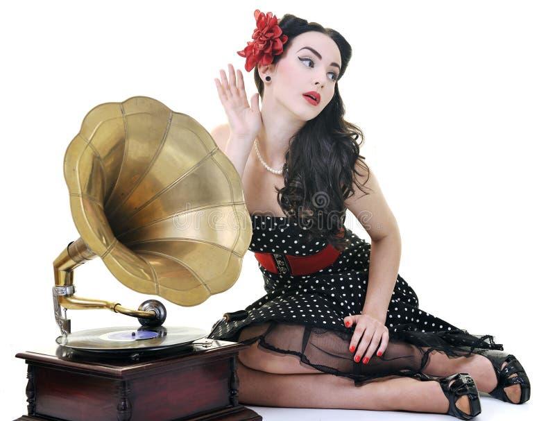 俏丽的在老留声机的女孩听的音乐 库存照片