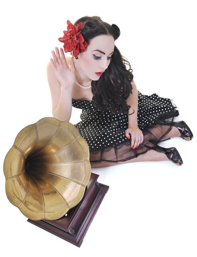 俏丽的在老留声机的女孩听的音乐 免版税库存图片