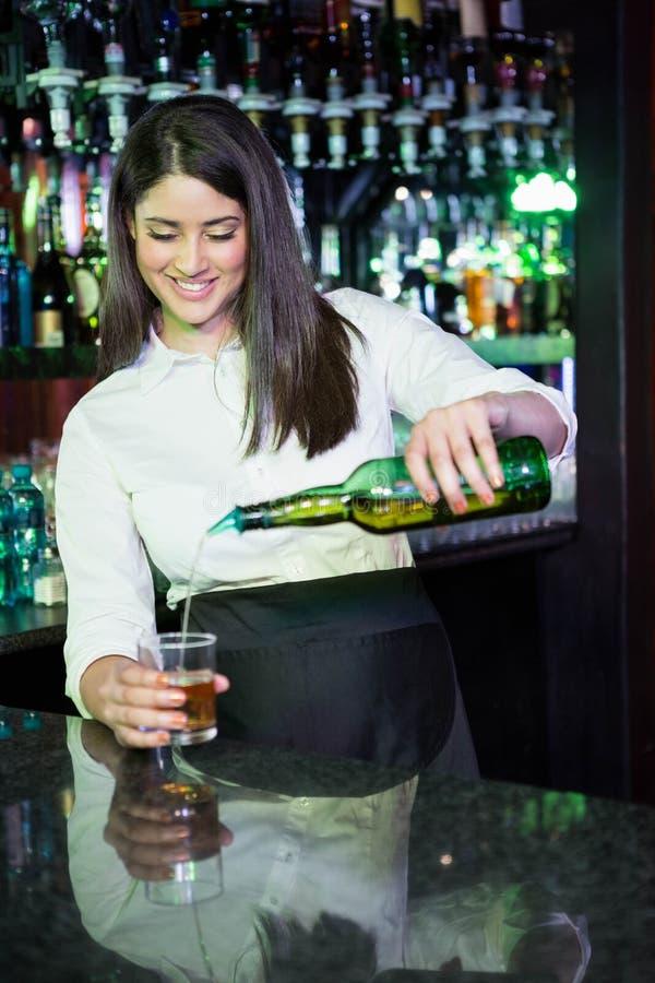 俏丽的在玻璃的侍酒者倾吐的威士忌酒 库存图片