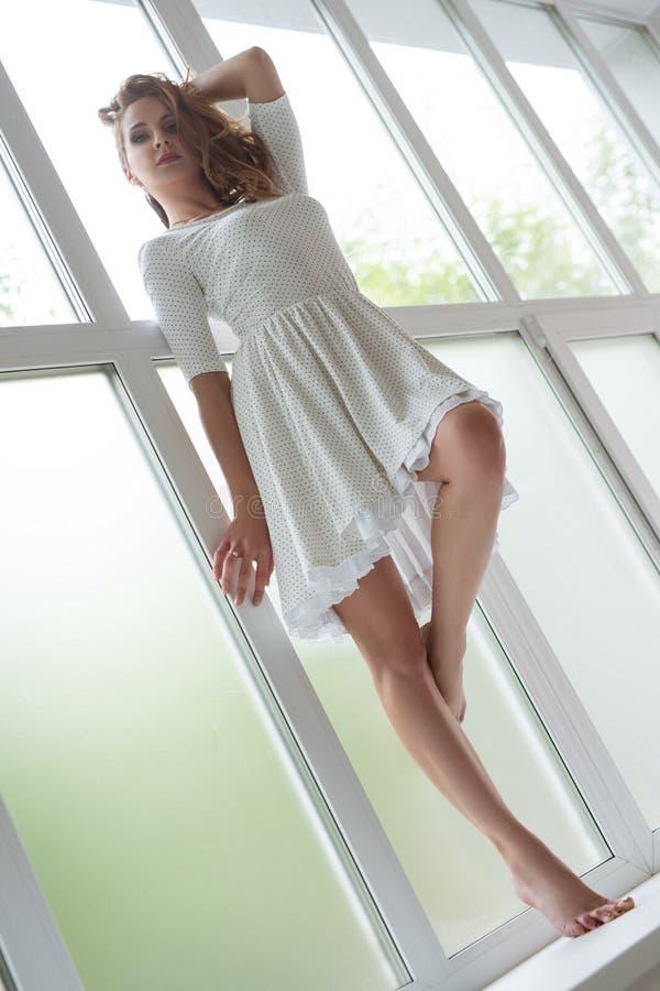 俏丽的夏天礼服的亭亭玉立的金发碧眼的女人在窗口基石 免版税库存图片