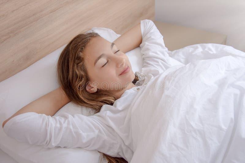 俏丽的夫人在床上在户内与闭上的眼睛 免版税库存照片
