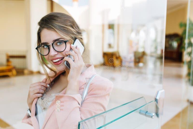 俏丽的女商人,少女微笑和谈话由电话,看与照相机,站立在大厅里 佩带时髦 免版税库存图片
