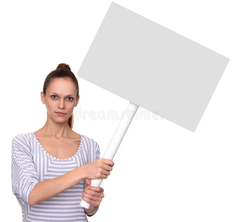 俏丽的女孩举行在棍子的一张空白的招贴 库存图片
