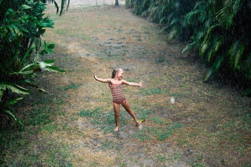 俏丽的女孩享受雨和跳舞在街道上在降雨量下在夏天 库存照片