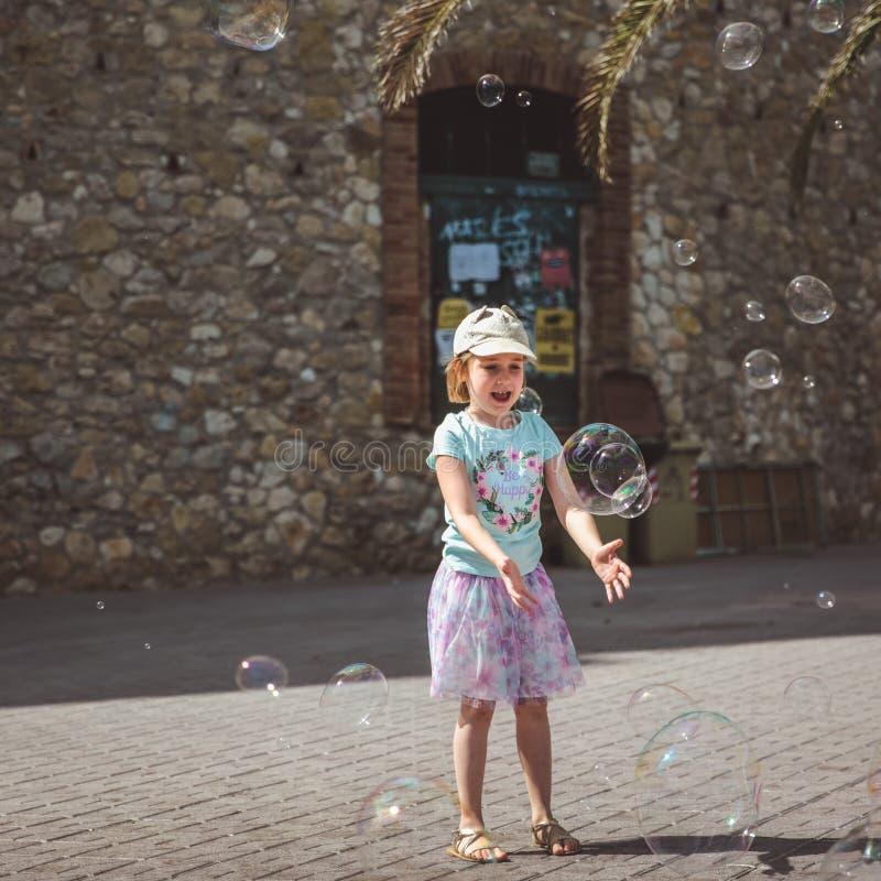 俏丽的女孩使用与在街道的大泡影在夏日 免版税库存照片