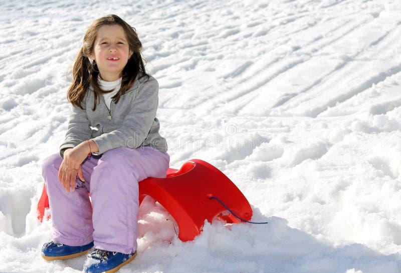俏丽的女孩使用与在雪的红色雪撬在冬天 库存图片