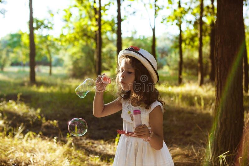 年轻俏丽的女孩吹的泡影,走在公园在日落 库存照片