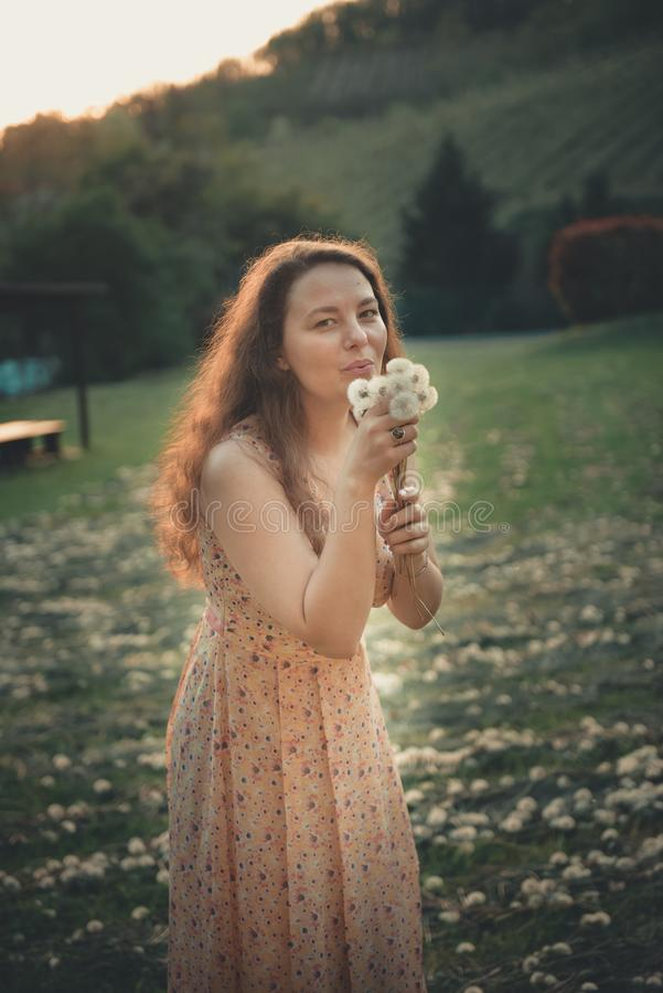 俏丽的女孩吹的蒲公英在夏天公园 免版税库存照片