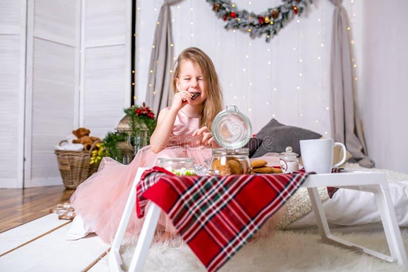 俏丽的女孩在一件桃红色礼服的4岁 孩子在有床的圣诞节屋子,吃糖果、巧克力、曲奇饼和饮料 库存照片