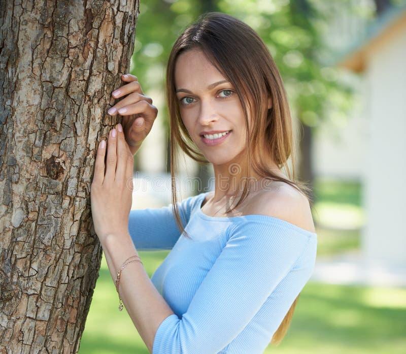 俏丽的女孩在城市公园微笑着 免版税库存照片