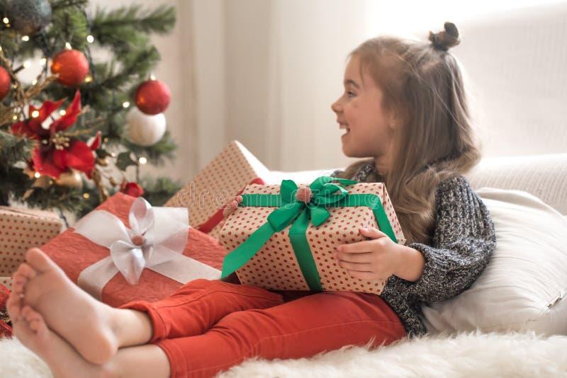 俏丽的女孩在她的屋子里拿着一个礼物盒并且微笑着,当在家时坐她的床 免版税库存照片