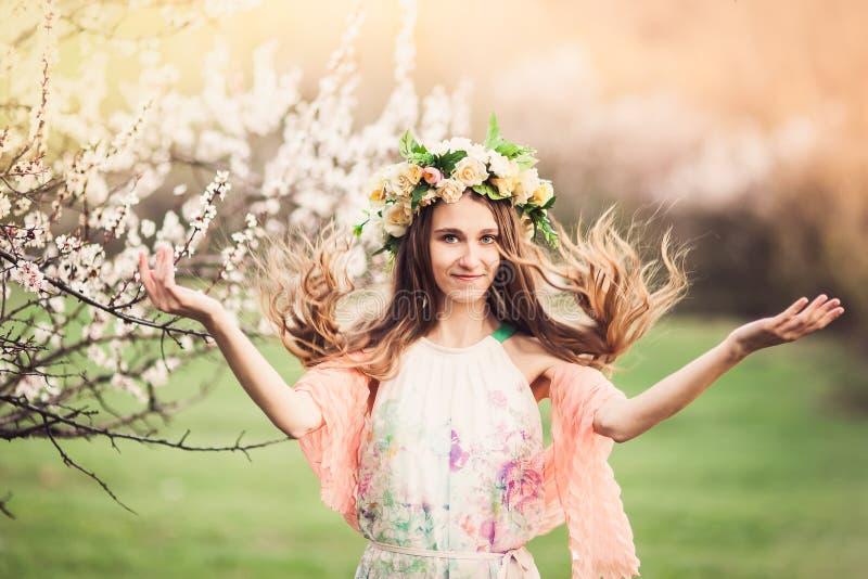 俏丽的女孩在春天开花庭院里 免版税库存图片