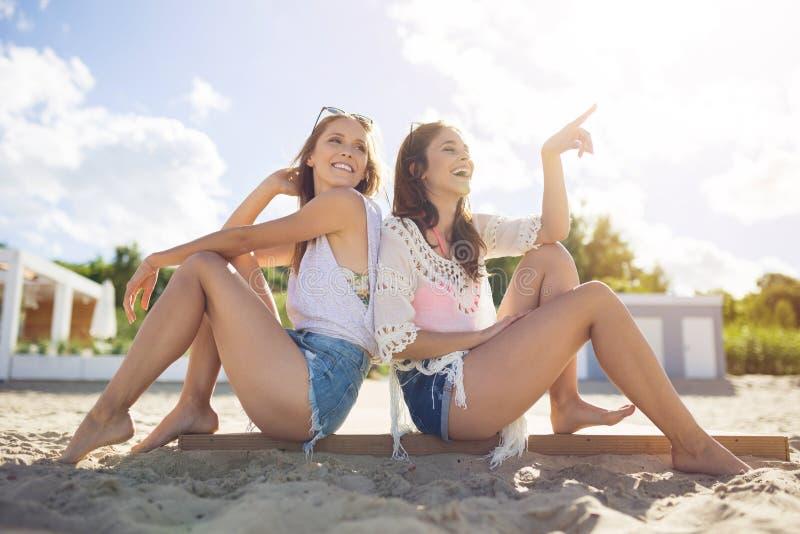 俏丽的女孩坐与指向某事的朋友的海滩 库存照片