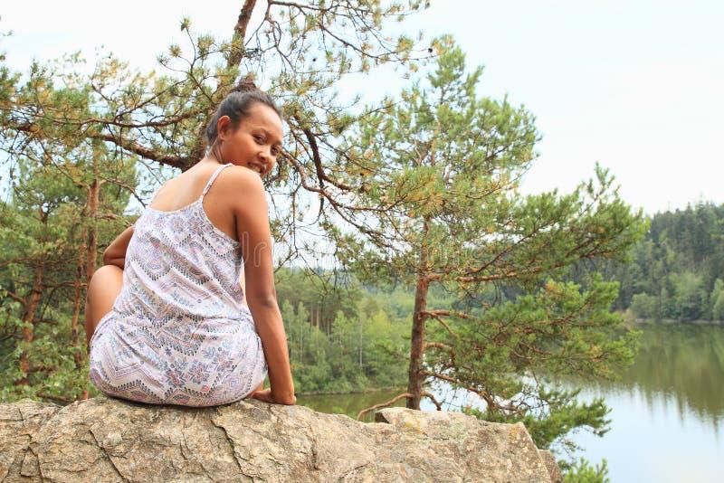 俏丽的女孩坐岩石由水 库存图片