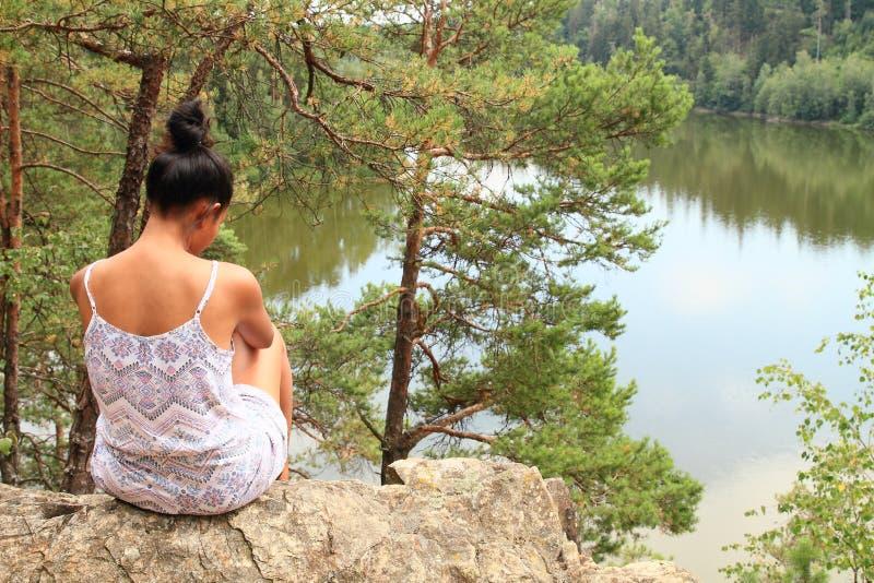 俏丽的女孩坐岩石观看的水 免版税库存图片
