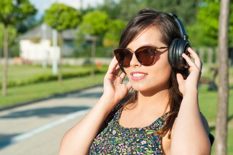 俏丽的女孩微笑的听到在耳机的音乐 免版税库存图片