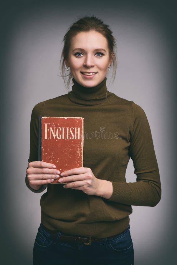 俏丽的女孩拿着英国课本 免版税库存图片