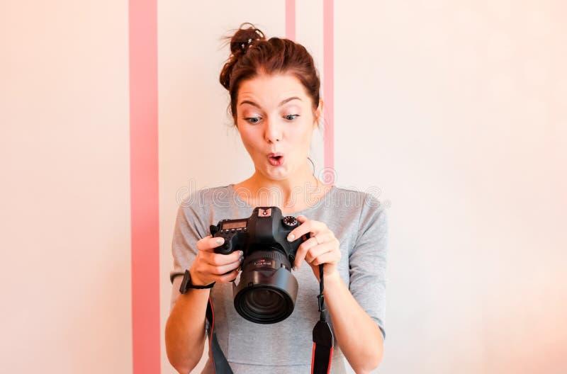 俏丽的女孩摄影师调查她的照相机并且做滑稽的惊奇的面孔 免版税库存图片