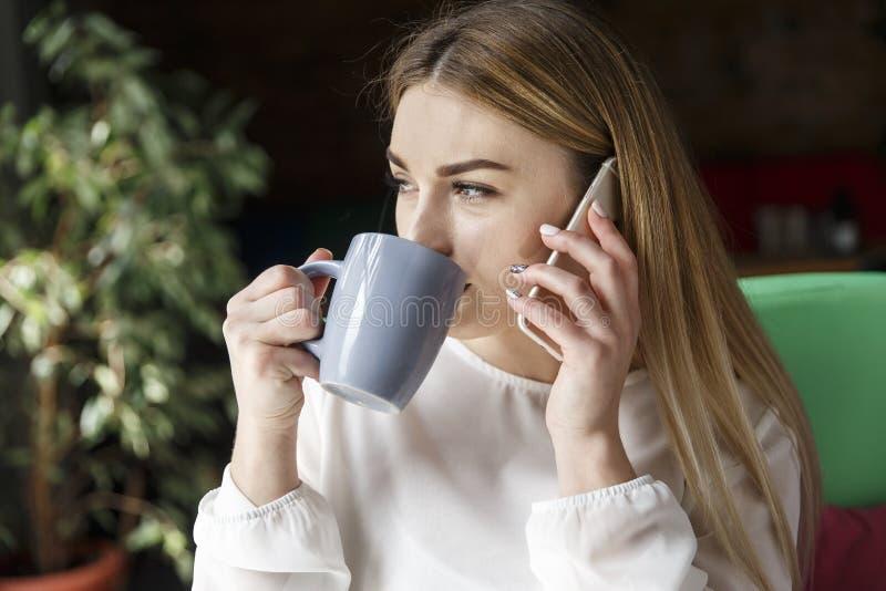 俏丽的女孩是坐和喝咖啡 她看窗口 女孩拿着接近耳朵的电话 她佩带企业随员 免版税库存图片