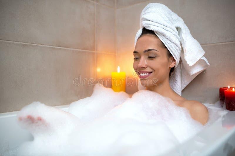 俏丽的女孩有松弛时光在浴,有些蜡烛,浴缸 免版税图库摄影