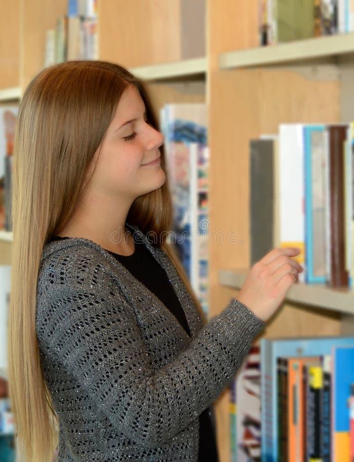 年轻俏丽的女孩浏览书 库存图片