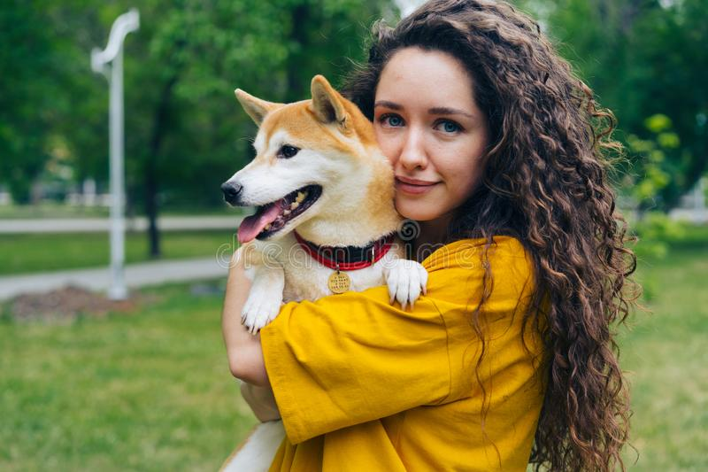 俏丽的女孩爱的狗所有者身分画象在有她美好宠物微笑的公园 库存照片
