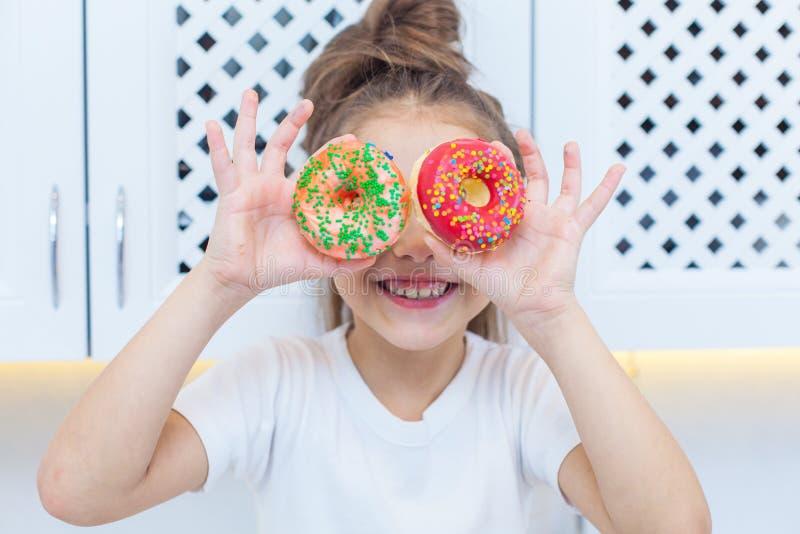 俏丽的女孩特写镜头用看通过在明亮的厨房背景的两个被洒的油炸圈饼的双重小圆面包  库存图片