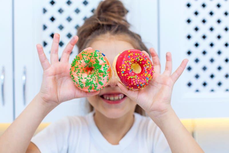 俏丽的女孩特写镜头用看通过在明亮的厨房背景的两个被洒的油炸圈饼的双重小圆面包  免版税库存图片