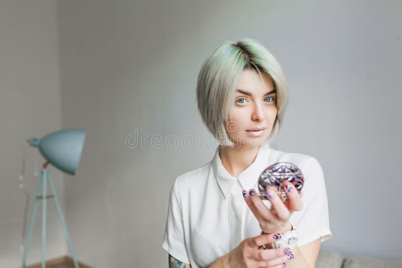 俏丽的女孩画象有灰色短的发型身分的在灰色演播室 她佩带白色礼服和轻的构成 她 库存图片