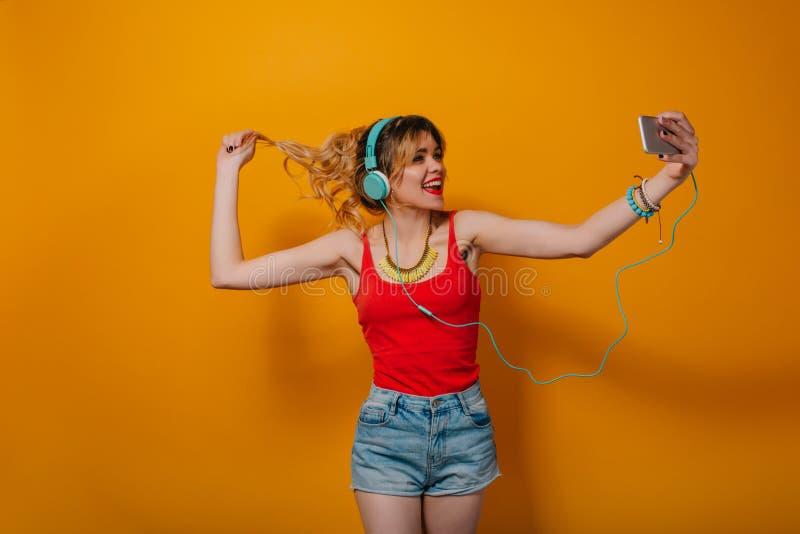 俏丽的女孩画象有长的卷发的在尾巴谈话在橙色背景的电话在演播室 她佩带红色T 库存照片