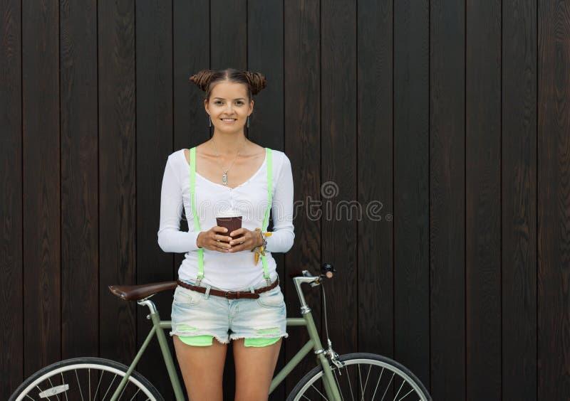 俏丽的女孩简而言之和与她的自行车的T恤杉立场在木板条明亮的晴天附近墙壁固定齿轮 免版税库存图片
