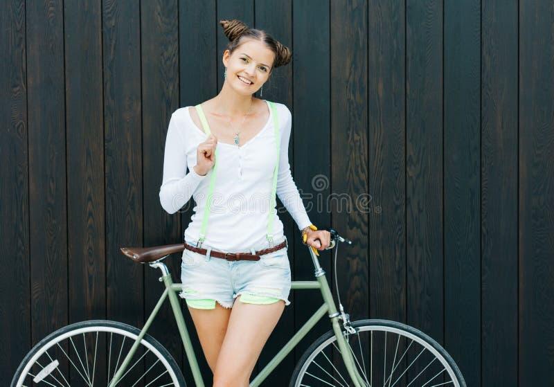 俏丽的女孩简而言之和与自行车的T恤杉立场在木板条明亮的晴天附近墙壁固定齿轮 免版税库存照片