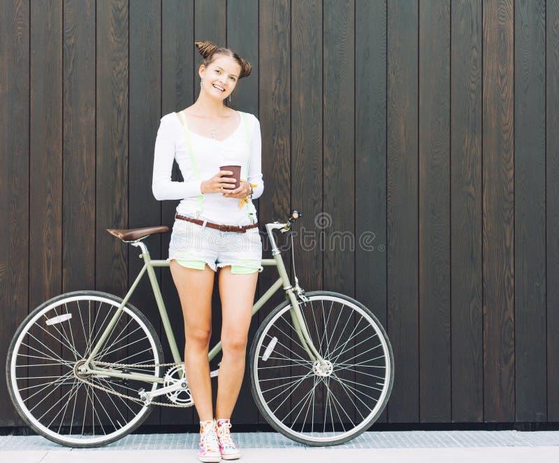俏丽的女孩简而言之和与自行车的T恤杉立场在木板条明亮的晴天附近墙壁固定齿轮 库存图片