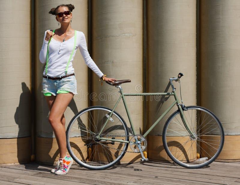 俏丽的女孩简而言之和T恤杉,在太阳镜立场与自行车固定齿轮摆在反对异常的墙壁o的背景 库存照片