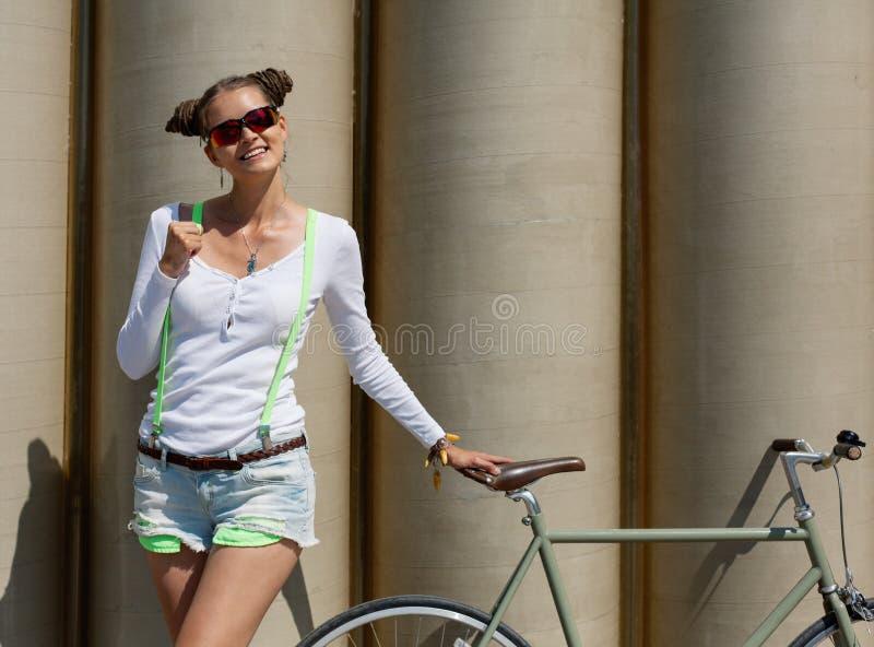 俏丽的女孩简而言之和T恤杉,在太阳镜立场与自行车固定齿轮摆在反对异常的墙壁o的背景 免版税库存图片