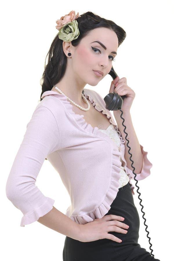 俏丽的女孩联系在老电话 库存图片