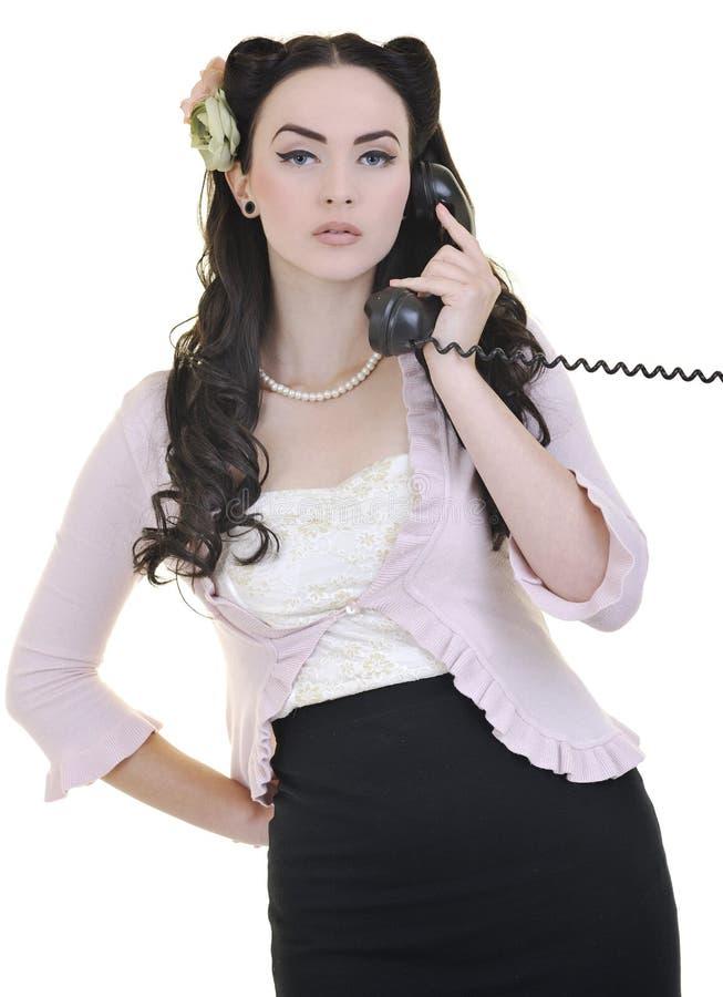 俏丽的女孩联系在老电话 免版税库存图片