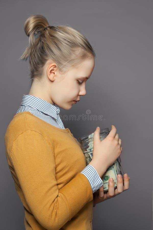 俏丽的女孩青少年和金钱在玻璃瓶子在灰色背景 库存照片