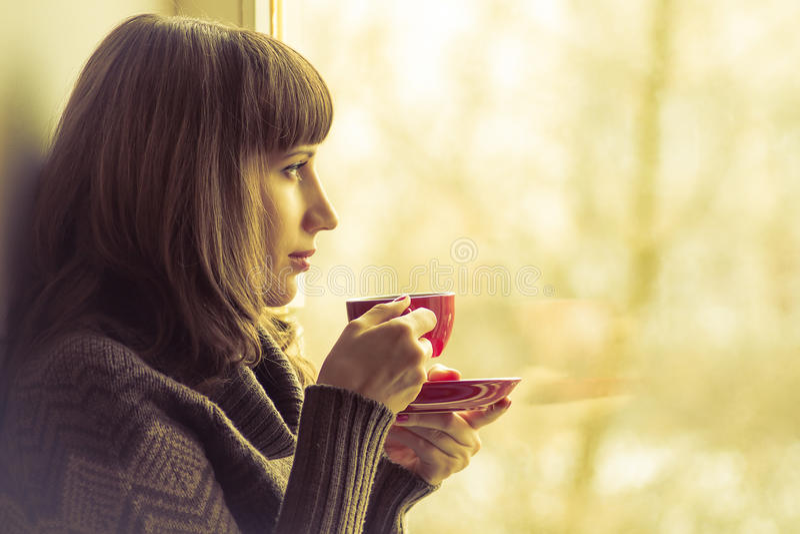 俏丽的女孩饮用的咖啡或茶在窗口附近 被定调子的温暖的颜色 免版税图库摄影