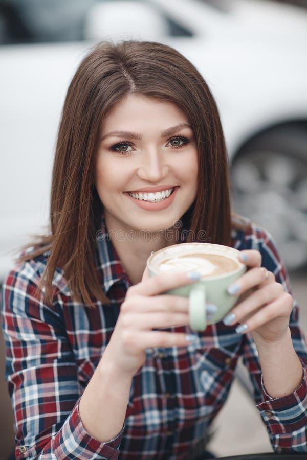 俏丽的女孩,有典雅的发型的美丽的浅黑肤色的男人在格子花呢上衣在夏天咖啡馆喝咖啡户外 库存照片