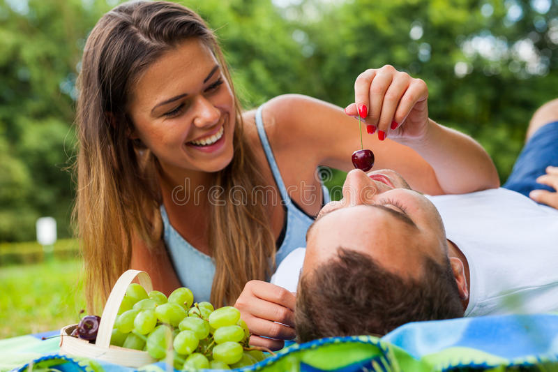 俏丽的女孩给樱桃她的男朋友 她喂养他 免版税库存图片