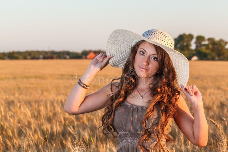 年轻俏丽的女孩画象在明亮的帽子穿戴了 免版税库存图片