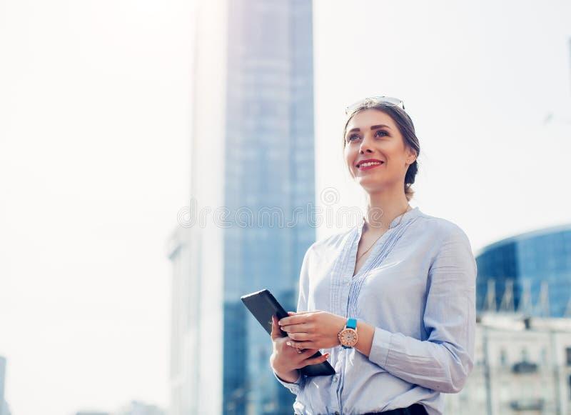 俏丽的女实业家画象聪明偶然的使用在商业中心愉快的成功的女实业家中的数字式片剂蓝色的 库存图片